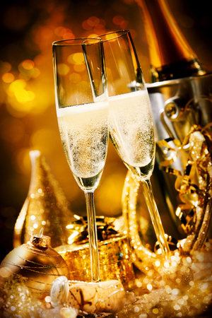 Two romantic effervescent flutes of champagne with luxury gold decorations and a horseshoe for luck in a festive still life for New Year, wedding, anniversary or Valentines
