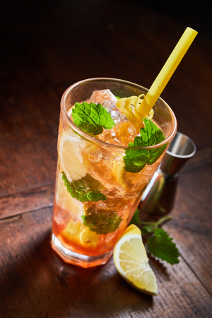 Ice cold refreshing mint julep cocktail with rum or bourbon, fresh lemon and mint blended on crushed ice and served in a tall glass viewed high angle on a wooden bar counter Stock Photo