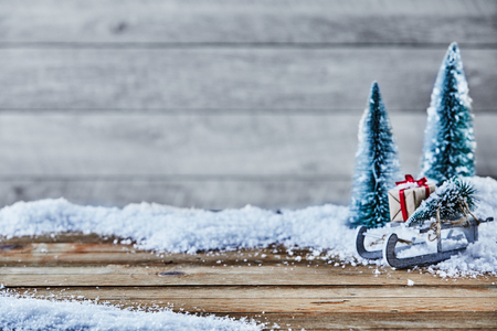 Christmas still life of a toy sled, gifts and fir trees on snow with large copy space on rustic wood for your advertising placement or greeting
