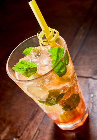 Glass of fresh mint julep cocktail with lemon blended with rum or bourbon whiskey and served on crushed ice