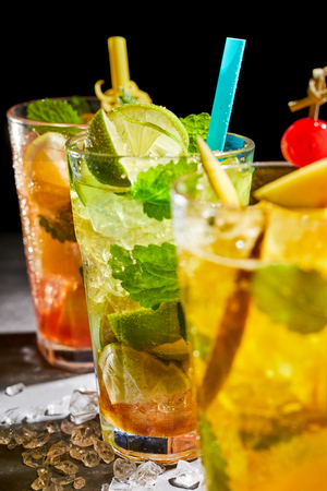 Delicious fresh mint julep cocktail with lime and a blend of rum or bourbon on crushed ice served in a tall glass