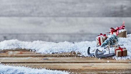 Festlicher Weihnachtshintergrund mit Winter schneien auf rustikalem Holz mit Raum für Produktplatzierung und eine Seitenanordnung des Schlittens, Baum und Geschenke mit weichem Unschärfehintergrund-Kopienraum Standard-Bild - 90094969