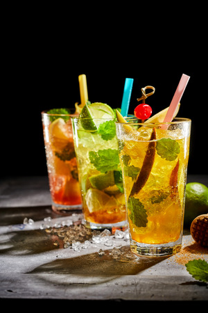 Three assorted fresh fruit cocktails served on crushed ice with mint including lime, orange and kiwifruit backlit with shadows and copy space