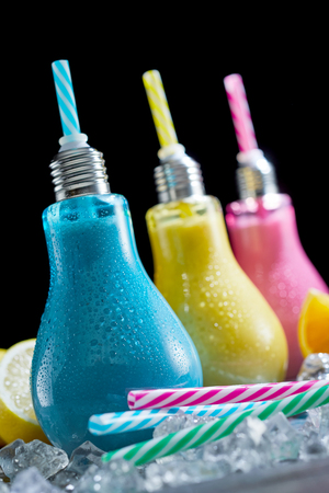 Fun chilled cocktails served in colored light bulb shaped glass containers with straws on a bed of crushed ice in a close up tilted view Stock Photo
