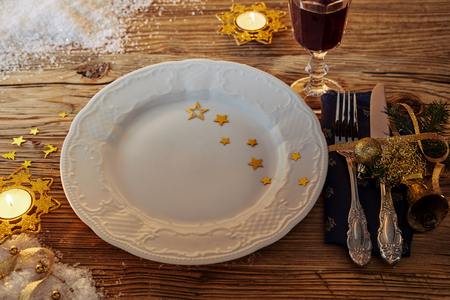 Festive Xmas table setting with stars on an empty white plate, burning candles a glass of red wine and decorative utensils and napkin with baubles and ribbon