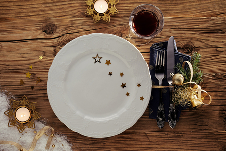 Decorative Christmas table setting with burning candles, an empty plate decorated wit stars, red wine and utensils and napkin tied with ribbon Stock Photo