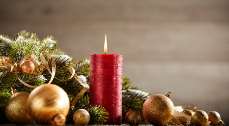 Traditional Christmas card with close-up of a red burning candle, golden baubles and fir branch against blurred background for copy space