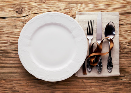 Simple Christmas place setting with utensils and a napkin decorated with a brown ribbon alongside a generic empty white plate on a wood table