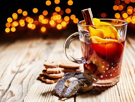 バック グラウンドでのパーティー ライトのきらめくボケ味と素朴な木のクッキー添えホット スパイシーなクリスマス gluhwein、または砂糖とスパイ 写真素材