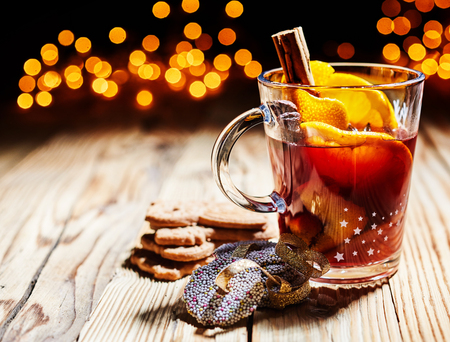 Hot spicy Christmas gluhwein, or mulled red wine with sugar and spices, served with cookies on rustic wood with a twinkling bokeh of party lights in the background Imagens