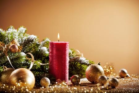 赤いろうそく、黄金のつまらないもののモミの枝とクリスマスの装飾的な背景
