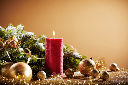 Decorative Christmas background with red candle, golden baubles and fir branches Stock Photo