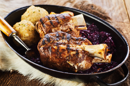Traditional German grilled pork hock with dumplings and red cabbage cooked on a winter barbecue and served in a pan