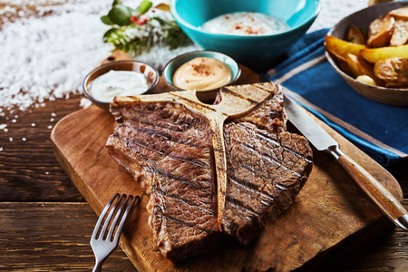 Piece of grilled t-bone steak on wooden cutting board in close up view