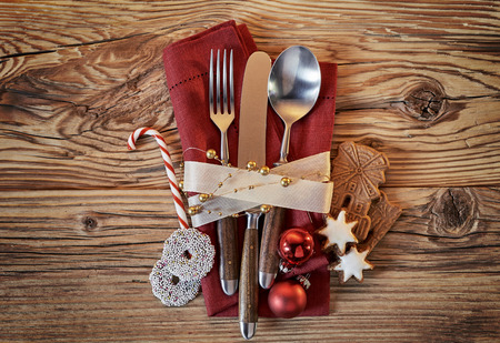 Christmas place setting with cookies and candy cane alongside a red napkin tied with knife spoon and fork on a rustic wood table viewed from overhead Stock Photo
