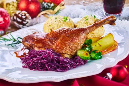 황금 구운 크리스마스 칠면조 다리와 야채는 휴가 시즌을 축하하기 위해 레스토랑에서 붉은 천으로 크리스마스 장식으로 둘러싸인 플래터에 제공