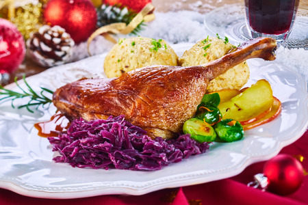 Golden roasted Xmas turkey leg and vegetables served on a platter surrounded by Christmas decorations on a red cloth at a restaurant to celebrate the holiday season Stock Photo