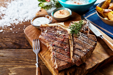 Piece of grilled t-bone steak on wooden cutting board with side dishes in close up view
