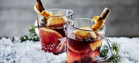 Panorama banner with two glasses of Christmas Gluhwein or mulled red wine garnished with stick cinnamon and served on winter snow with copy space