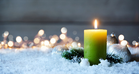 Candle burning on snow with bokeh lights in background