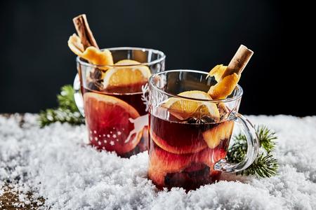 おいしい温めた赤ワイン、またはグルーワイン、オレンジとシナモンは、クリスマスシーズンを祝うために冬の雪のベッドの上でメガネで提供