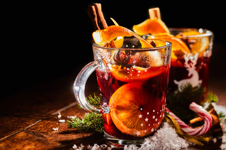 Traditional Christmas Gluhwein or mulled sweet spicy red wine with cinnamon served in two glass mugs with candy canes and copy space
