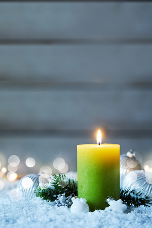 Christmas candle burning on snow in vertical image with bokeh lights in background
