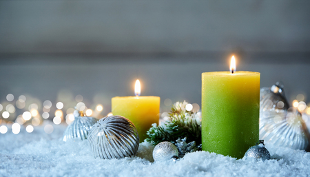 Two burning Christmas candles and decorations on snow with bokeh lights Stock Photo