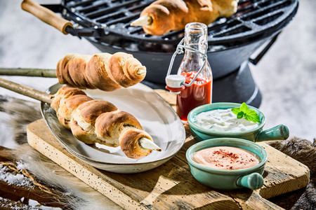 Winter barbecue with grilled twist bread on wooden skewers served on a wooden board above snow with dipping sauces and ketchup Stock fotó