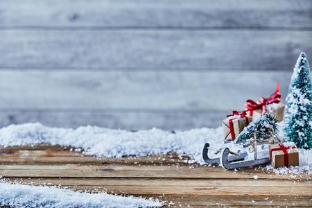 背景コピースペースと製品配置のための前景スペースを持つ素朴な木材に対して雪の上にそり、木やギフトの装飾とクリスマス静物