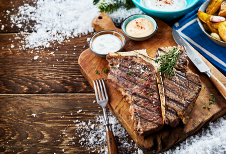 Grilled t-bone steak with sauces and side dishes on wooden board against table