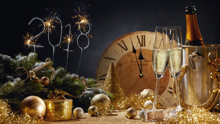 2018 festive golden New Year still life with sparkler date, clock ready to strike midnight, decorations and two flutes of sparkling champagne