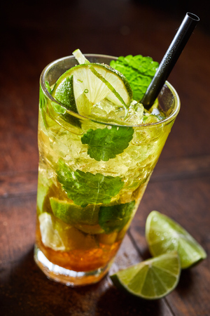 Iced lime cocktail with fresh mint leaves served with crushed ice and a straw in a tall glass on a wooden counter in a pub or nightclub Foto de archivo