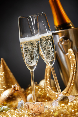 New Year card with two champagne flutes surrounded by golden Christmas ornaments during romantic party or celebration at midnight