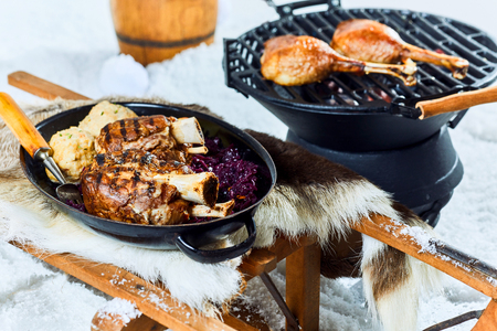 Wholesome grilled pork hocks with dumplings from a winter barbecue served with red cabbage in a pan on a bed of fresh snow Stockfoto