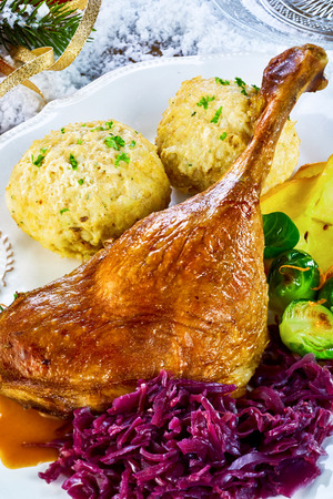 Golden roasted turkey or goose leg with dumplings, red cabbage and Brussels sprouts for a traditional Thanksgiving or Christmas dinner