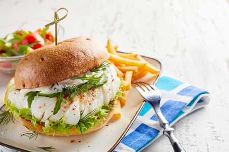 Spicy fish burger with fresh rocket and mayonnaise on a crusty toasted bun served with French fries and salad