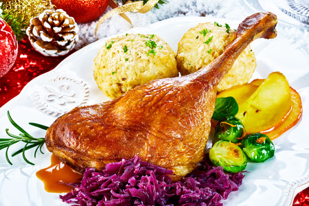 Crispy golden roasted Christmas turkey leg served with fresh vegetables and dumplings on a table set with Xmas decorations in a close up view