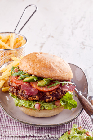 Pork belly burger with fresh avocado and crispy fried bacon, rocket, tomato ad lettuce on a crusty bun served with potato chips with copy space