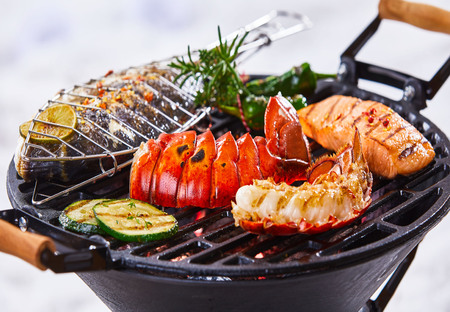 Gourmet seafood winter barbecue with crayfish tails, salmon and whole marine fish grilling over hot coals in a close up view Imagens