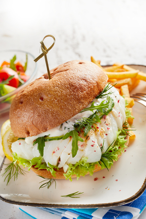 Close-up of a tasty fish burger served on plate with French fries and vegetables salad