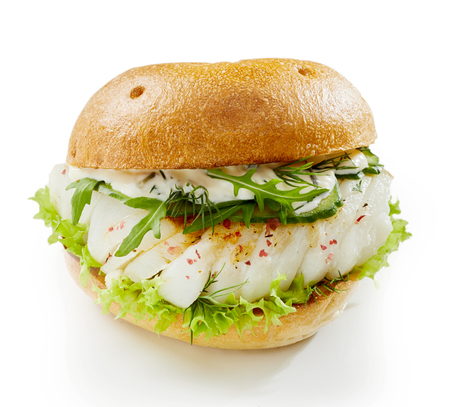 Healthy fish burger with rocket and mayonnaise seasoned with spice and served on a toasted bun over a white background Stock Photo