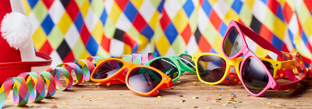 Brightly colored party background banner with multicolored fun sunglasses, streamers and confetti against a harlequin patterned backdrop