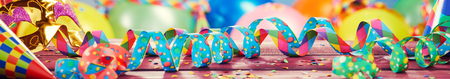 Colorful party, carnival or holiday banner with multicolored twirled ribbons or streamers, balloons and confetti in a wide panorama