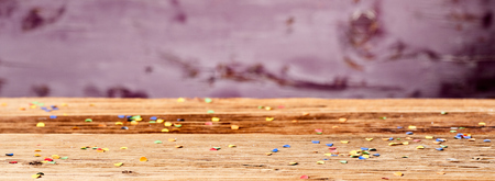 Party concept of colorful confetti scattered on wooden surface Banque d'images