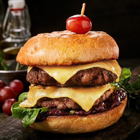 Close-up of a tasty double hamburger with cheese and deep fried ground meat on a wooden table against black background with copy space