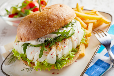Gourmet fish seafood burger with mayo and fresh salad greens and herbs on a crusty bun with side serving of potato chips