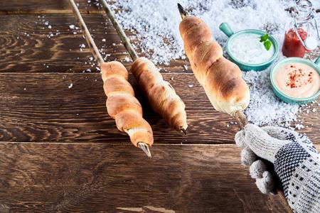 장갑 낀 손 흩어져 겨울 눈과 디핑 소스 그릇 나무 테이블 위에 막대기에 꼬치 구이 빵을 들고
