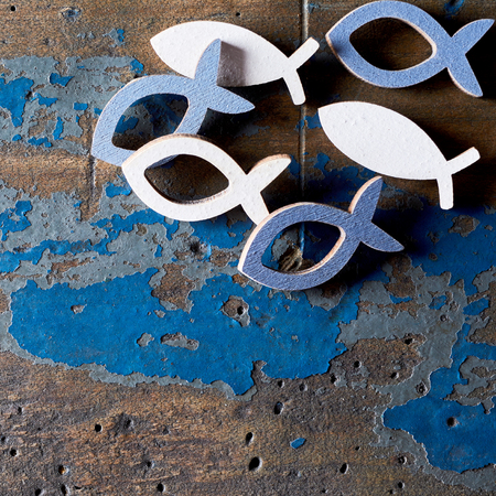 Closeup of metal Christian fish shapes on old blue and brown wood background