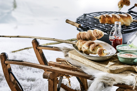 Rustic outdoor winter barbecue in snow with crusty twist bread on wooden skewers, dips and ketchup on a wooden table Stock fotó